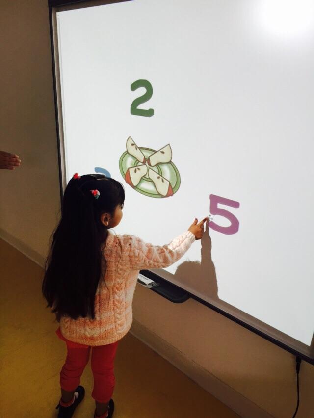 Niñas y niños participan activamente en pizarra interactiva del Jardín Infantil.